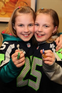 Riley and Erin Kovalcik in Seahawk shirts and hearing aids.