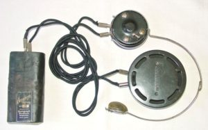 Figure 4.  Acousticon Model A carbon hearing aid with separate headphone, held to the ear with a spring headband.  Photo from: http://www.hearingaidmuseum.com/gallery/Carbon/Acousticon/info/acousticonmodela.htm