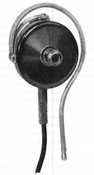 "Figure 5.  Early hearing aid ""receiver.""  This configuration, with a shaped wire to hold it to the ear rather than a headband, had a nubbin to which some type of earmold could be affixed.  Additionally, it was considerably reduced in size from earlier headphones, allowing for the elimination of the headband.  (Photo from Berger, 1974)."