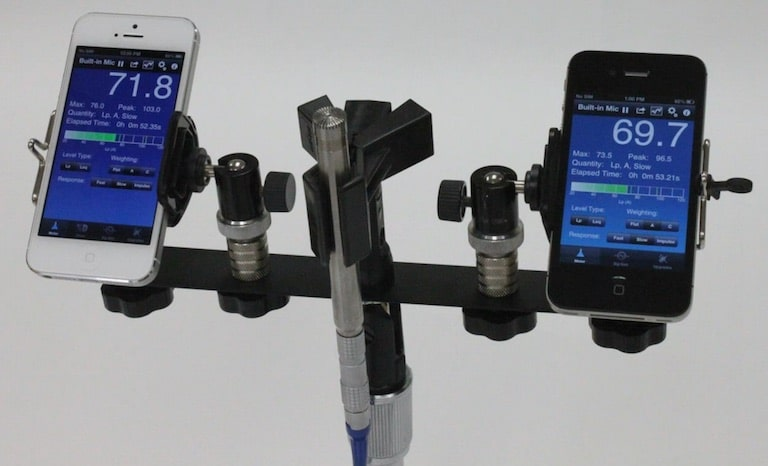 "Figure 3. A suggested procedure for measuring and comparing smart phone sound level meter (SLM) apps. The SoundMeter app on the iPhone 5 (left) and iPhone 4S (right) compared to ½"" Larson-Davis 2559 random incidence type 1 microphone (center). From Kardous and Shaw, 2014). The smartphones were attached to a stand in the middle of the reverberant sound chamber at a height of 4 feet, and about 6 inches from the reference microphone."
