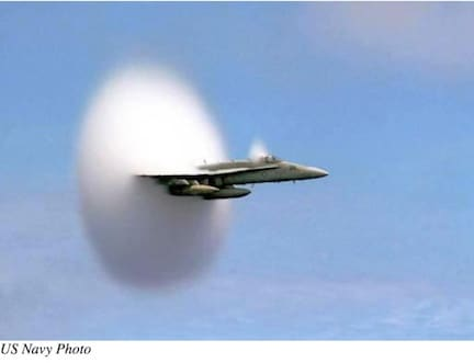 Figure 6. Mach cone visible as water vapor in the air gets trapped between pressure waves, and it briefly condenses, causing a cloud of condensed vapor to form a halo around the object. Photo made by Navy Ensign John Gay on July 7, 1999 while aboard the carrier USS Constellation, as Navy Lt. Ron Candiloro flew by.